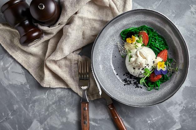 Burratasalat mit erdbeeren und meerespflanze, auf einem grau. salat mit burattakäse auf einer grauen platte und einem konkreten marmor.