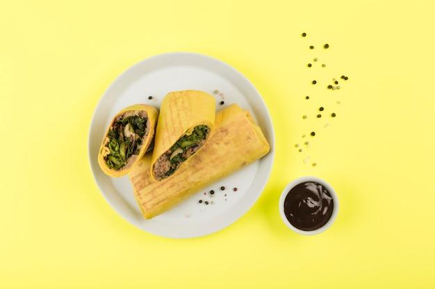 Burrito mit fleisch in einem fladenbrot auf einem leuchtenden gelb