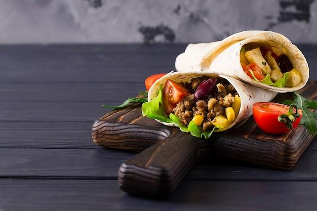 Burrito mit rindfleisch und gemüse auf einem holzbrett.