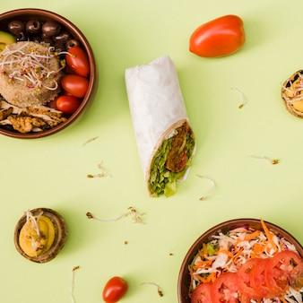 Burrito wrap mit reis; pilz gefüllt; salat und dessert auf grünem hintergrund