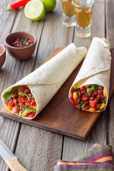 Burritos mit fleisch, bohnen, mais, tomaten, zwiebeln und chili. mexikanische nahrung. rezept.