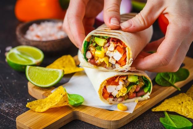 Burritos verpackt mit huhn, bohnen, mais, tomaten und avocado auf holzbrett