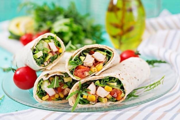 Burritos verpackt mit huhn und gemüse auf hellem hintergrund. hähnchen-burrito