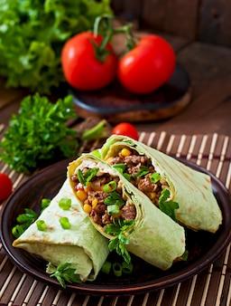 Burritos wickelt mit hackfleisch und gemüse auf einem hölzernen hintergrund ein