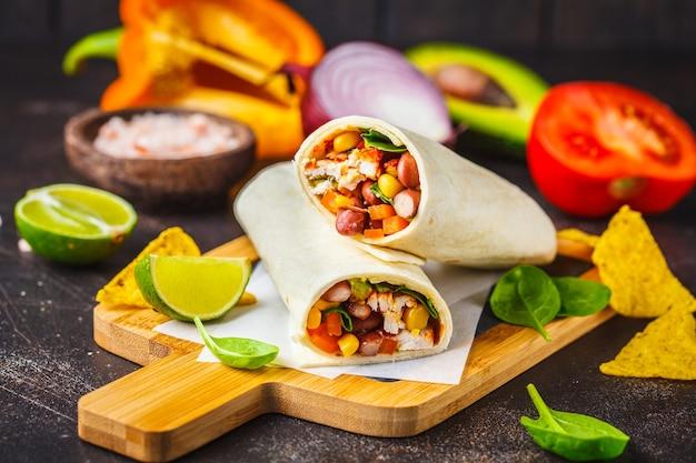 Burritos wickelt mit huhn, bohnen, mais, tomaten und avocado auf einem holzbrett, dunkler hintergrund ein. fleisch burrito, mexikanisches essen.