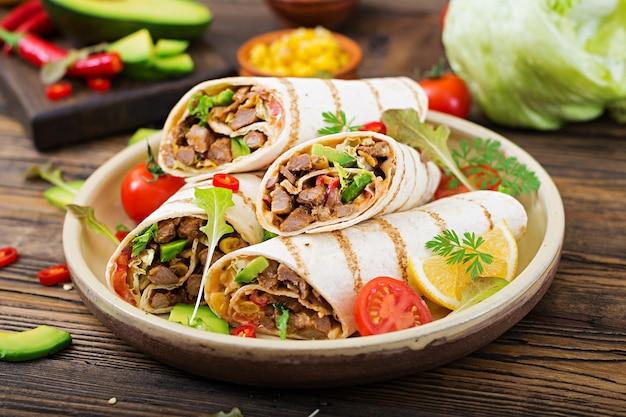 Burritos wickelt mit rindfleisch und gemüse auf einem hölzernen hintergrund ein. rindfleisch burrito, mexikanisches foo