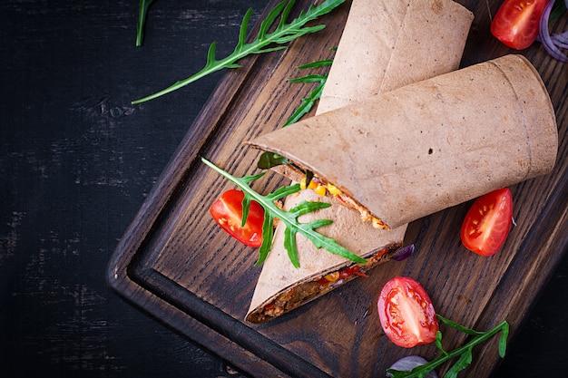 Burritos wraps mit rindfleisch und gemüse auf dunklem holzhintergrund. rindfleisch-burrito, mexikanisches essen. ansicht von oben, oben
