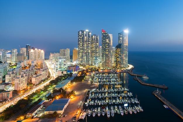 Busan-stadtskylineansicht an haeundae-bezirk, gwangalli-strand mit yachtpier bei busan, südkorea.