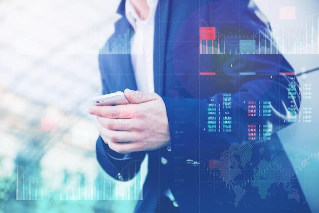 Business analytics mit dashboard-konzept für key performance indicators. geschäftsmann in einer blauen jacke hält ein smartphone in den händen.