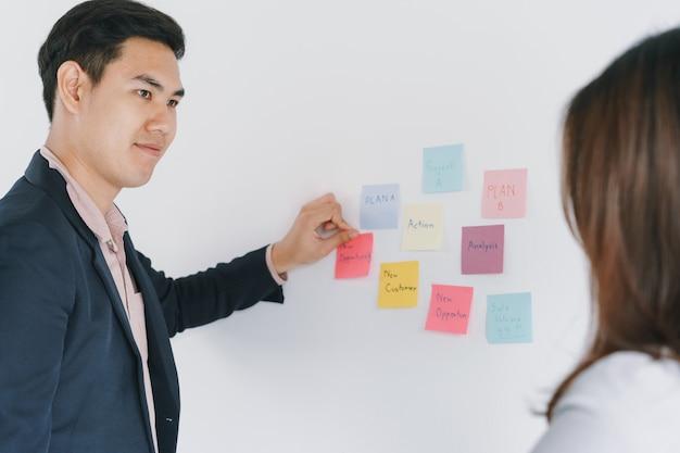 Business asian zwei personen treffen sich im büro und verwenden haftnotizen, um die idee zu teilen