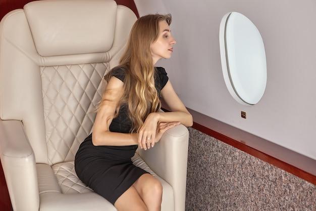 Business-class-passagier im flugzeug. eine schlanke junge frau sitzt in einem privatjet am fenster.