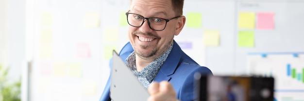 Business-coach, der auf das online-konzept für den geschäftskurs mit der handykamera zeigt camera