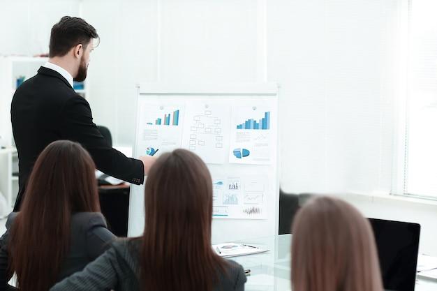 Business coach, der mitarbeiter auf dem whiteboard bei der unternehmensschulung unterrichtet.