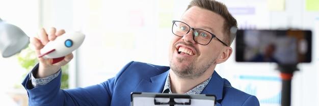 Business coach startet spielzeugrakete vor dem geschäftsinnovationskonzept der handykamera