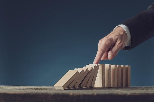 Business crisis manager stoppt den zusammenbruch von dominosteinen mit dem finger. über blauem hintergrund mit kopierraum.