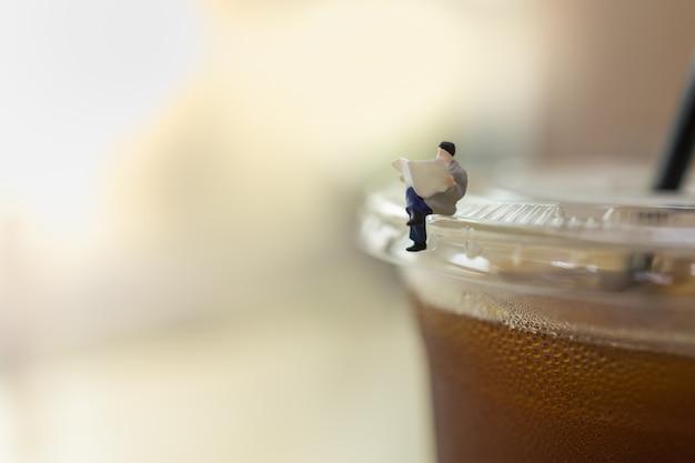 Business, entspannungskonzept. schließen sie herauf von geschäftsmann-miniaturfigurmenschen, die sitzen und zeitung auf plastikbecher zum mitnehmen des schwarzen eiskaffees mit kopienraum lesen.