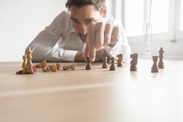 Business executive macht strategie für die zukunft, indem sie schwarze und weiße schachfiguren gegeneinander positioniert, wobei die meisten weißen mit linseneffekt gefallen sind