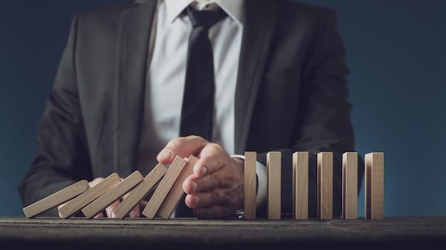 Business executive stoppt zusammenbrechende dominosteine mit seiner hand
