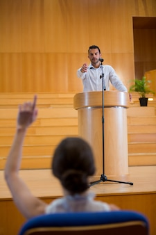Business executive zeigt auf das publikum, während er eine rede hält