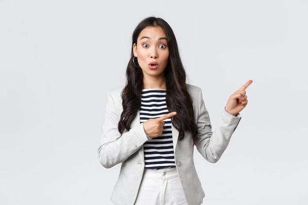 Business, finanzen und beschäftigung, konzept für erfolgreiche unternehmerinnen. faszinierte geschäftsfrau, asiatischer immobilienmakler, der mit den fingern nach rechts zeigt und neugierig aussieht, findet ein gutes geschäft