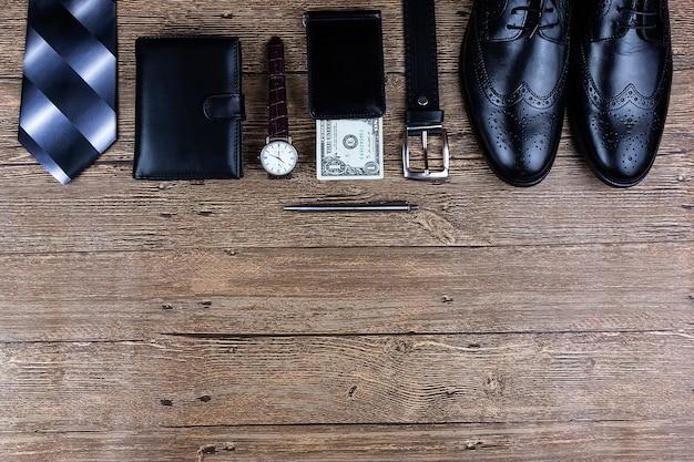 Business flat lag hintergrund mit einem kopierraum. herrenschuhe, armbanduhr, brieftasche, gürtel und eine krawatte auf hölzernem hintergrund.