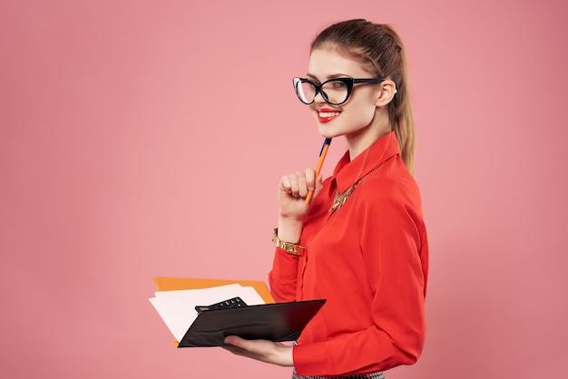 Business-frau im roten hemd mit notizblock in händen emotionen rosa hintergrund. foto in hoher qualität