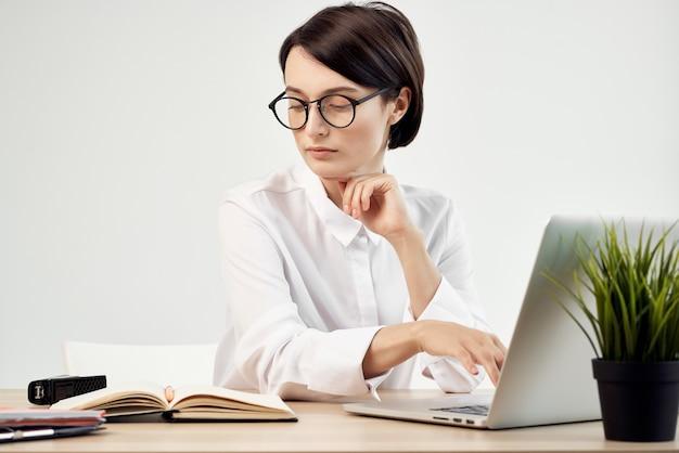 Business-frau im weißen hemd sitzt am arbeitstisch vor laptop-büro