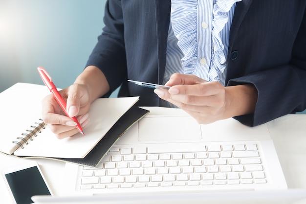 Business-frau in dunklen anzug mit kreditkarte, mit laptop und writting auf notebook, business-und online-shopping-konzept