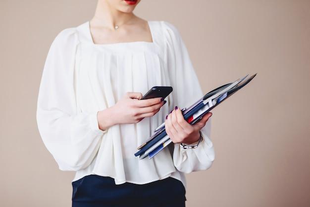 Business-frau-messaging am telefon mit dokumenten in ihren händen