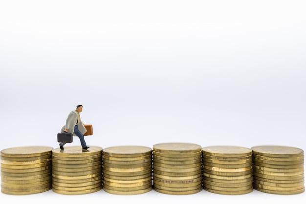 Business, geld, finanzen und management. geschäftsmann miniaturfigur läuft auf der reihe der stapel von goldmünzen.