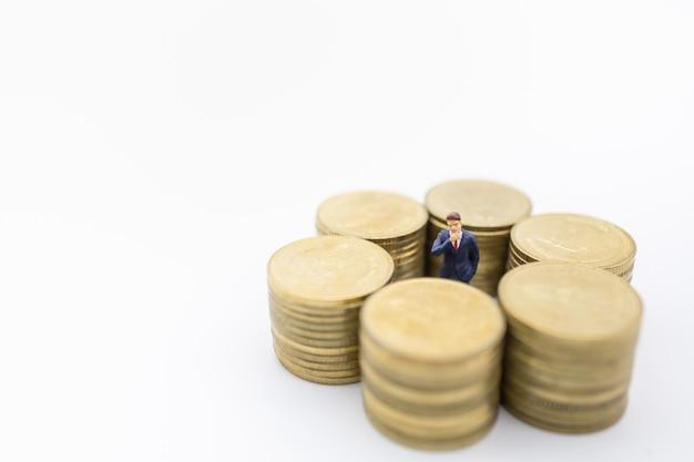 Business, geld, finanzen und management. schließen sie oben von der stehenden mitte der geschäftsmannminiaturzahl der reihe des stapels goldmünzen.