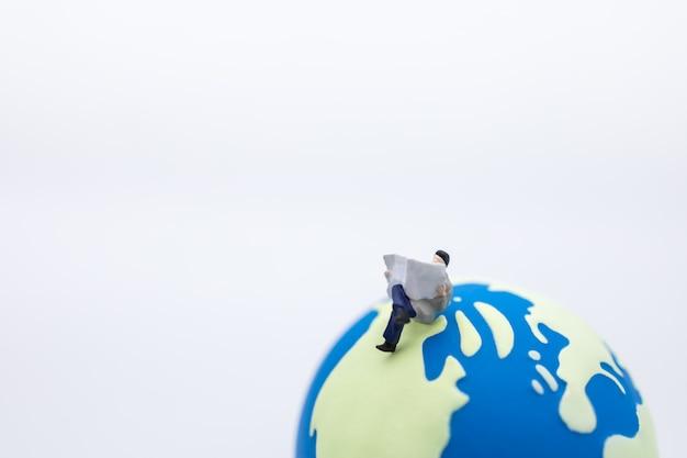 Business, global und bildung. schließen sie oben von der geschäftsmannminiaturzahl, die eine zeitung auf miniweltball sitzt und liest.