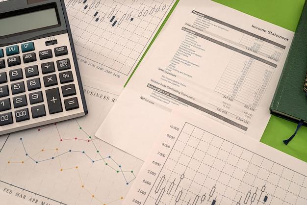 Business-grafiken geldrechner-stift-notizbücher, die auf dem tisch liegen. grafikkonzept