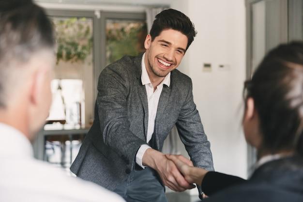 Business-, karriere- und vermittlungskonzept - glücklicher europäischer mann im anzug, der sich freut und der gruppe von mitarbeitern die hand schüttelt, als er während des interviews im amt eingestellt wurde
