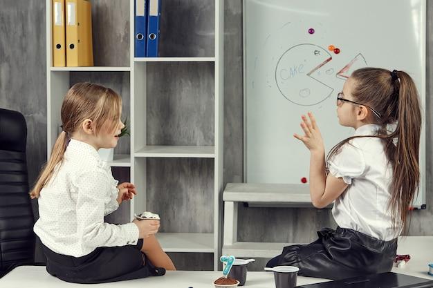 Business-kids-mädchen chatten, während sie auf dem tisch sitzen