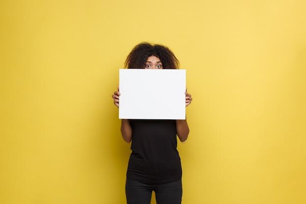 Business-konzept - close up portrait junge schöne attraktive african american lächelnd zeigt plain weiß leere zeichen. gelbe pastellstudio hintergrund. platz kopieren