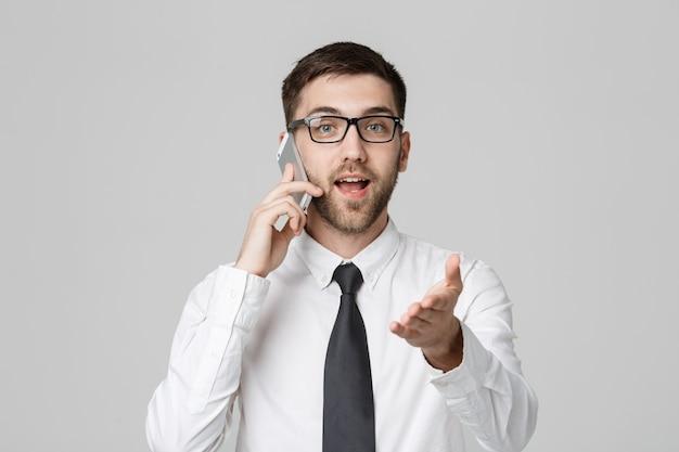 Business-konzept - porträt junge hübsche angry geschäftsmann im anzug sprechen am telefon blick in die kamera. weißer hintergrund.