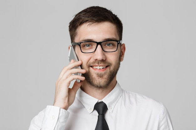 Business-konzept - porträt junge hübsche fröhliche geschäftsmann im anzug sprechen am telefon blick in die kamera. weißer hintergrund. text kopieren