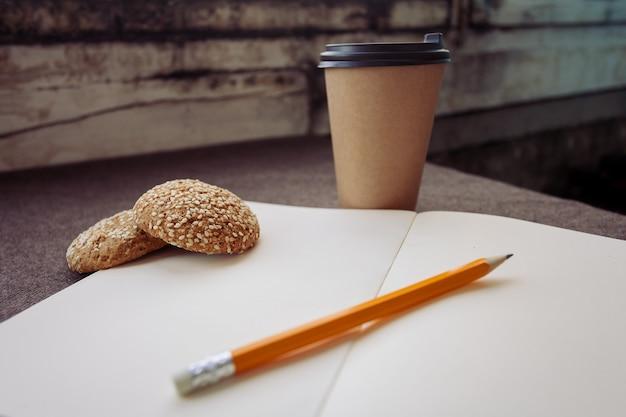 Business-, lifestyle-, lebensmittel- und kaffeekonzept - bleistift, notizbuch und papierkaffeetasse auf braunem stoffhintergrund