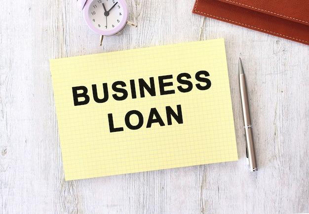 Business loan text in einem notizbuch geschrieben, das auf einem hölzernen arbeitstisch liegt