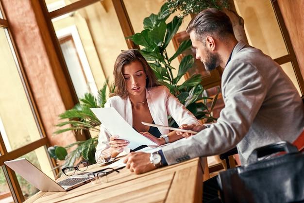 Business-lunch-geschäftsleute, die am tisch in der restaurantfrau sitzen und dem mann die projektidee erklären