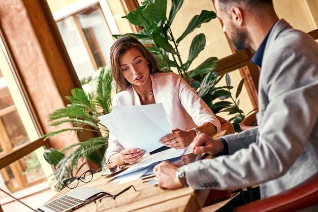 Business-lunch-geschäftsleute, die am tisch in der restaurantfrau sitzen und den betreffenden vertrag betrachten