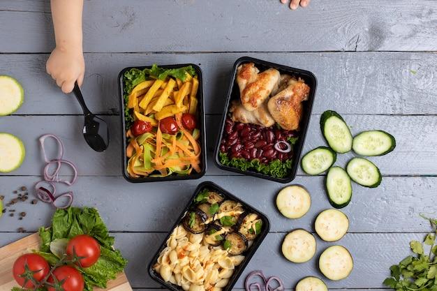 Business-lunch in essensboxen, brathähnchenflügeln, gedünstetes gemüse, gedünstetes fleisch, fertiggericht zu essen