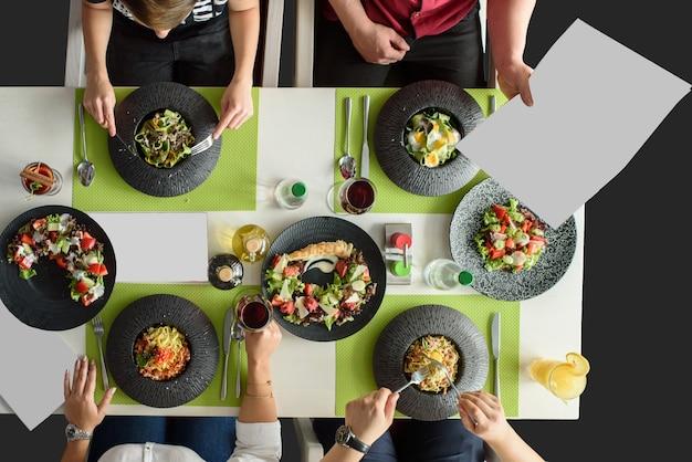 Business lunch italienische pasta für große gesellschaft von kollegen. leckeres essen auf dem schwarzen teller. freunde treffen.