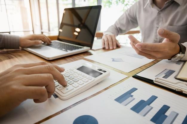 Business-man-analyse-daten-dokument mit buchhalter berechnung über gebührensteuer in einem büro