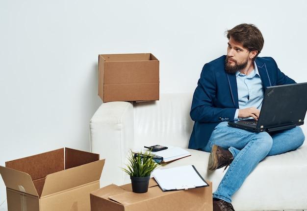 Business-mann-boxen mit dingen laptop-arbeit auspacken professional