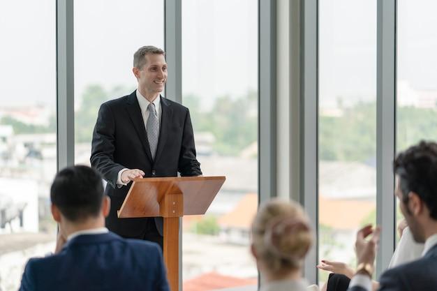 Business-mann-coach-sprecher, der auf einer seminarveranstaltung mit einer gruppe unterschiedlicher zielgruppen über arbeit und erfolg im geschäft spricht