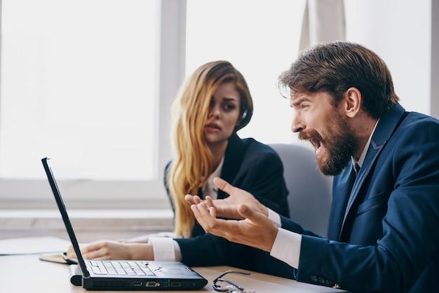 Business-mann und frau im büro vor einem laptop-karriere-arbeitsprofis