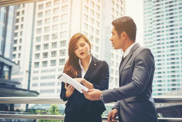 Business-mann zeigt auf dokument mit lächeln und diskutieren etwas mit ihrem kollegen, während vor dem büro zu stehen.