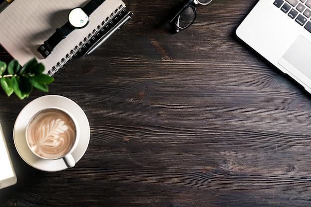 Business-schreibtisch mit laptop und telefon notebook stift brille smartwatch auf dunklem holztisch, modernen arbeitsplatz tischplatte hintergrund mit geräten und kaffeetasse, draufsicht von oben
